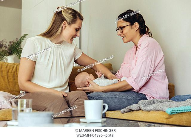 Midwife and mother giving newborn baby a belly massage to help with digestion