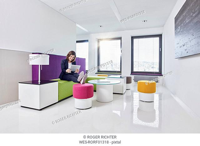 Young businesswoman using tablet in office lounge