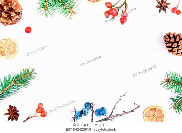 Christmas winter or Happy New Year decoration background. Natur frame composition made from christmas tree branches, pine cones and colorful berries on a rustic...