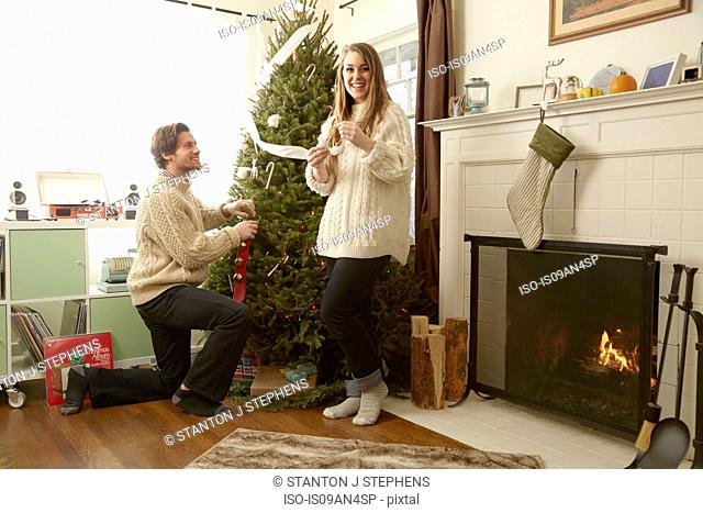 Young couple preparing decorations for christmas tree
