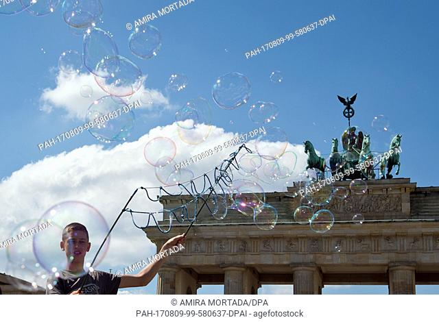 Soap bubble artist Steve from Poland standing in front of the Brandenburg Gate in Berlin, Germany, 9 August 2017. Photo: Amira Mortada/dpa