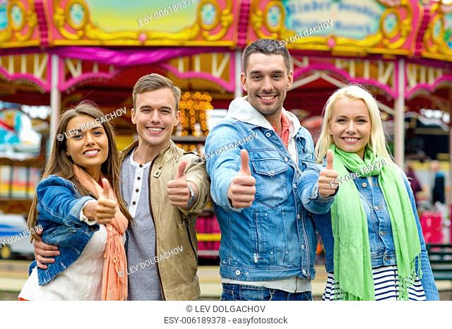 leisure, amusement park and friendship concept - group of smiling friends showing thumbs up with carousel on the back