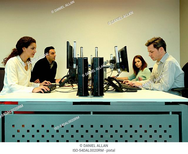 Business people using computers at desk