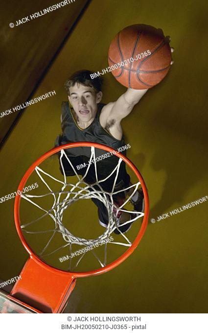 Basketball player about to slam dunk the ball