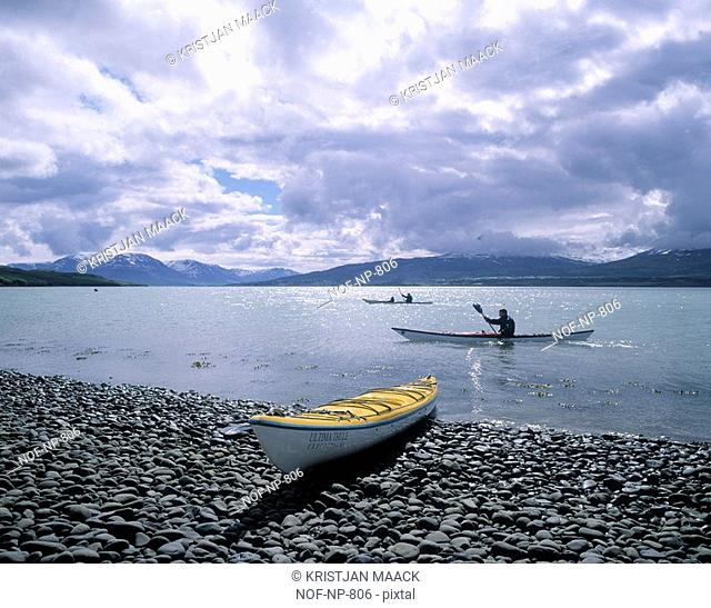 Kayakers rowing along the coastline