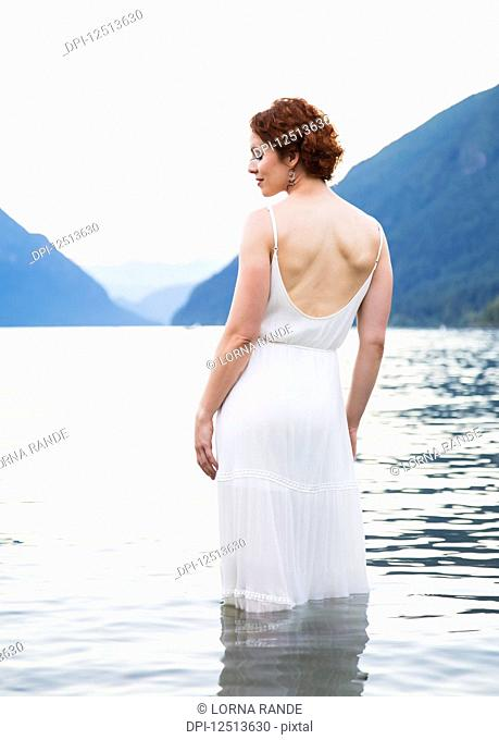 A woman with red hair and a white dress stands in the tranquil water of Alouette Lake on a summer evening; British Columbia, Canada