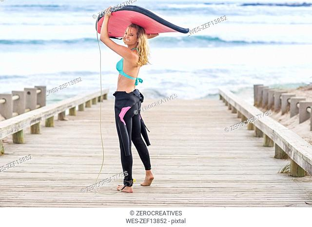 Woman walking to beach with surfboard