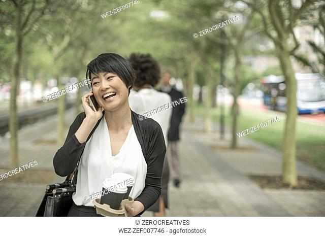 Young Asian woman carrying takeaway coffee and talking on the phone