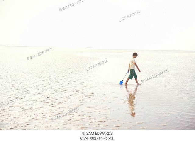 Boy walking with shovel in wet sand on overcast summer beach