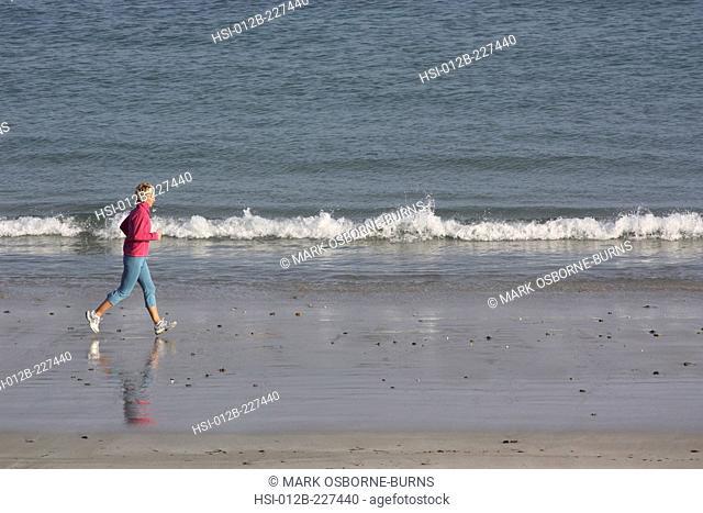 Blonde woman outdoors. Jogging along beach