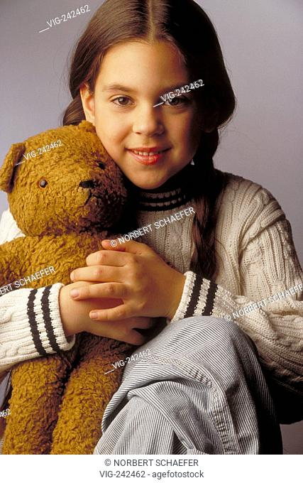 portrait, indoor, close-up, smiling 8-year-old girl with long brown plaits wearing a white pullover and striped jeans with her teddy  - GERMANY, 15/02/2005