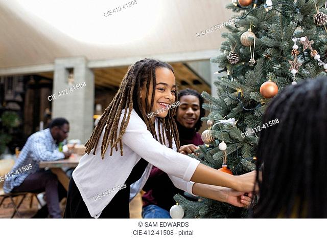 Happy girl decorating Christmas tree with family
