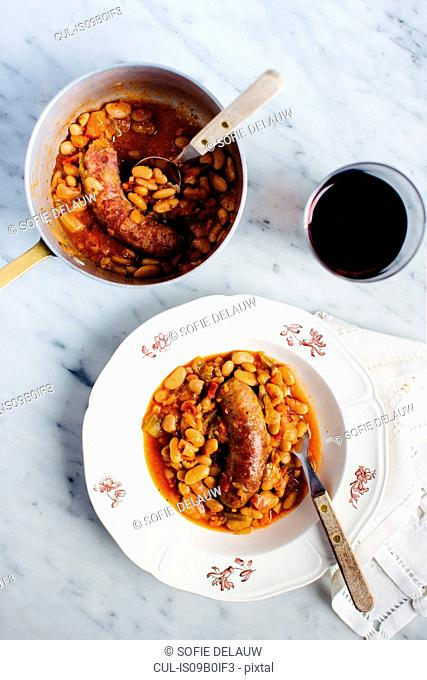 Overhead view of sausage with white beans in tomato sauce, Italian cuisine