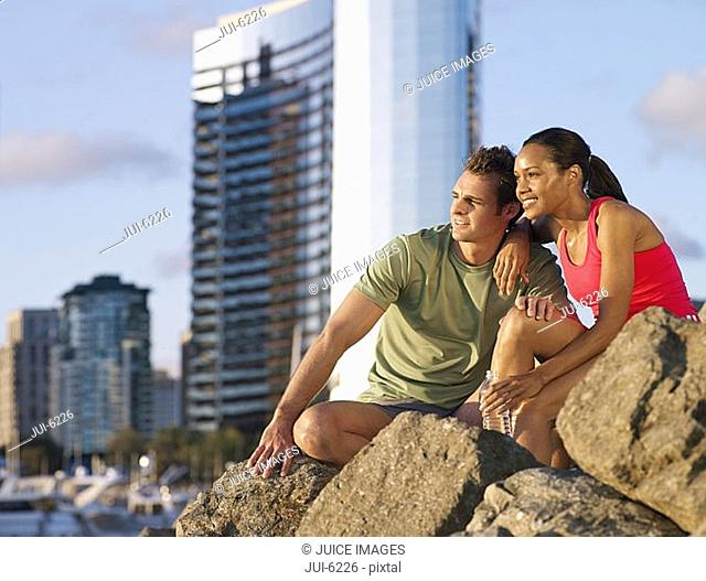 USA, California, San Diego, sporty couple sitting on rock overlooking harbour, smiling, side view