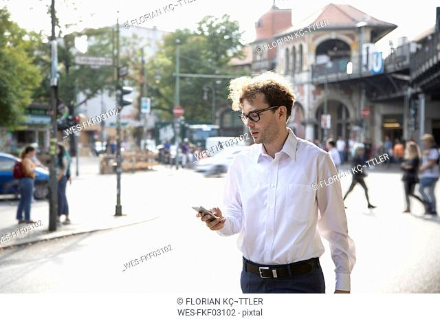 Germany, Berlin, businessman looking at cell phone outdoors