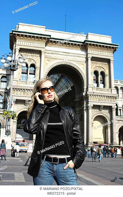 29 year old woman using cell phone in front of Galleria Vittorio Emanuelle II, Piazza del Duomo, Milan. Lombardy, Italy
