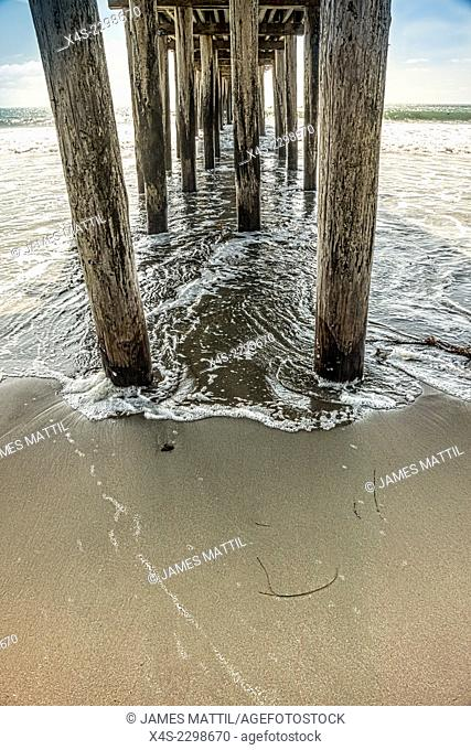 As the tide rises waves wash onto the sand beneath a wooden pier