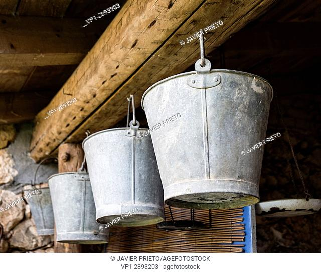 Three typical brass kettles hanging from a wooden beam in a country house. Country Cottage. Valladolid. Ribera del Duero. Spain
