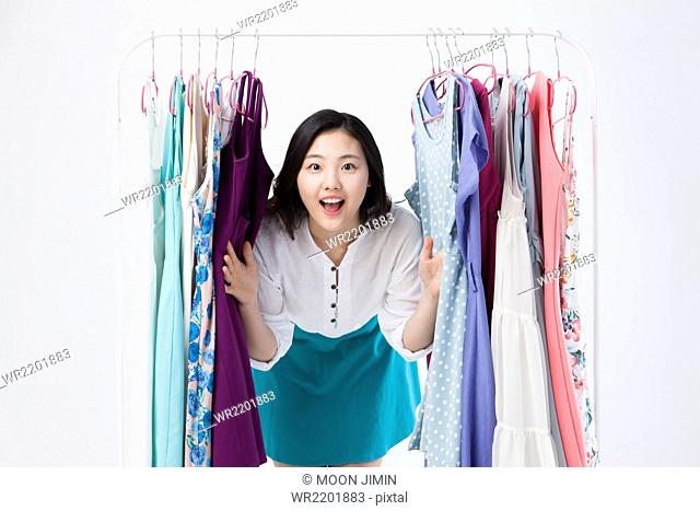 Young woman smiling between colthes on a hanger