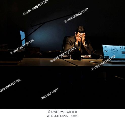Overstressed businessman sitting at his desk in the dark