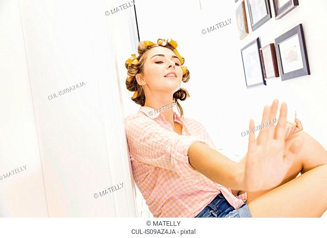 Young woman, foam rollers in hair, painting fingernails