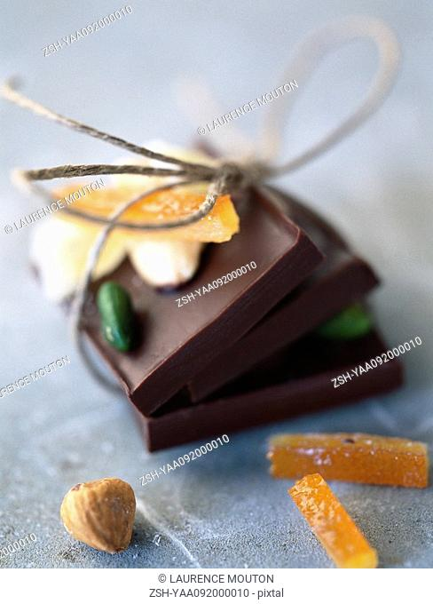 Chocolate bars tied together with string, candied fruit, hazelnut