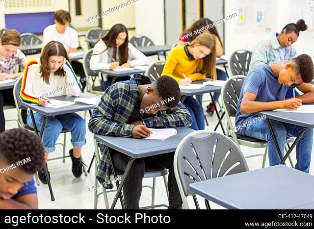 Focused high school students taking exam at desks in classroom