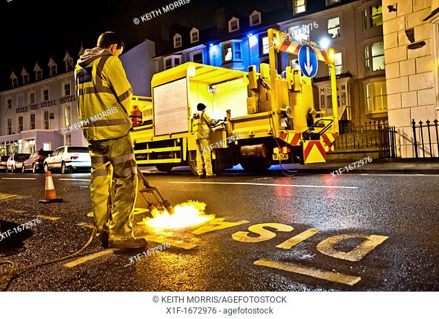 Men working using a flame gun setting out road markings at night on a street, Aberystwyth, Wales UK