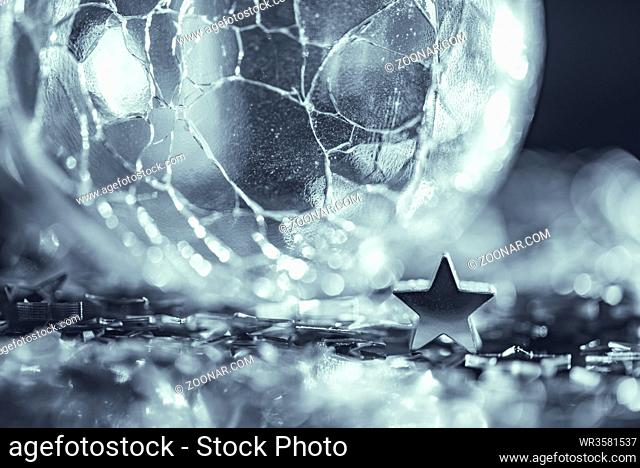 Macro photo of cracked glass sphere silver star with light bokeh