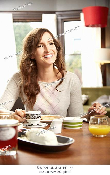 Young woman drinking breakfast coffee in kitchen