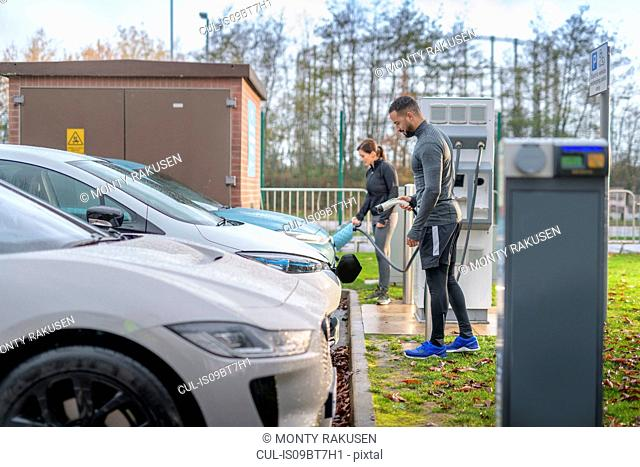 Sportsman and woman charging electric car at charging bay, Manchester, UK