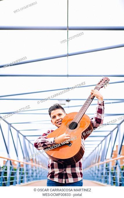 Gypsy boy playing guitar on a bridge