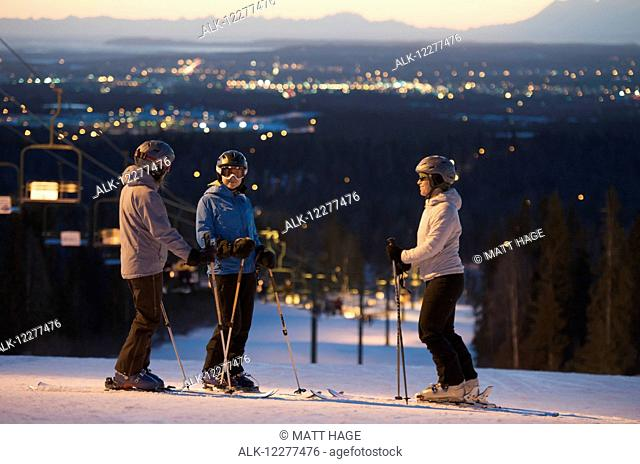 Friends at the top of Hilltop Ski Area at sunset in Anchorage, Alaska