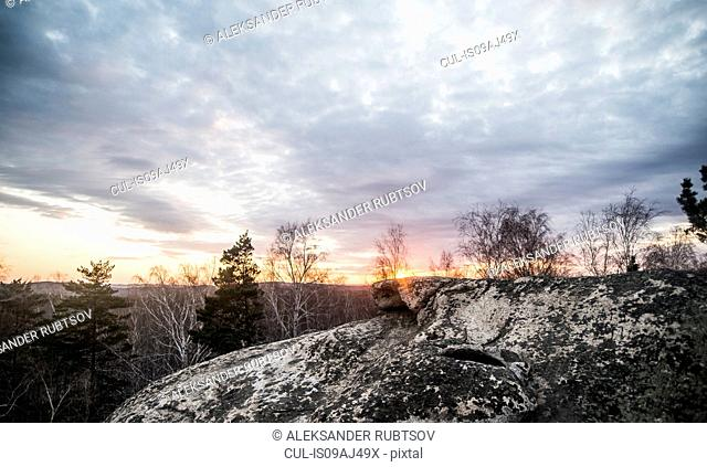 Rock formation and tree tops at sunset