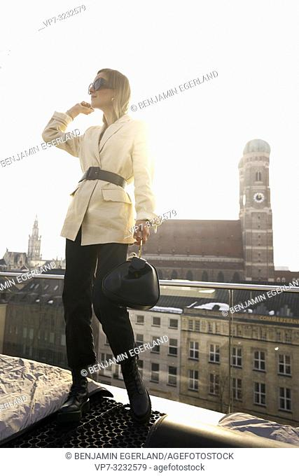 fashionable blogger woman on balcony next to church Frauenkirche, Marienkirche in city Munich, Bavaria, Germany