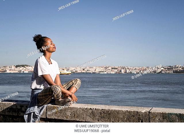 Young woman sitting on a wall at the waterfront with closed eyes, Lisbon, Portugal