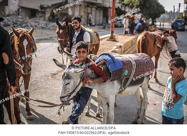 13 August 2019, Syria, Arihah: A young Syrian boy holds a donkey on the third day of Eid al-Adha. Eid al-Adha is the holiest feast in Islam