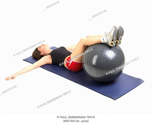 Woman exercising with fitness ball, studio shot