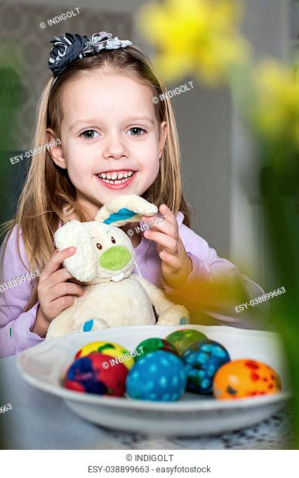Happy little girl with toy bunny and easter eggs. Easter, holiday and child concept
