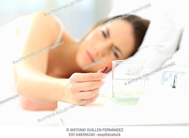 Ill woman hand holding a painkiller pill lying on a bed