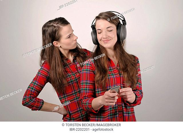 Twin sisters, one holding an iPod and listening to headphones, the other looking enviously