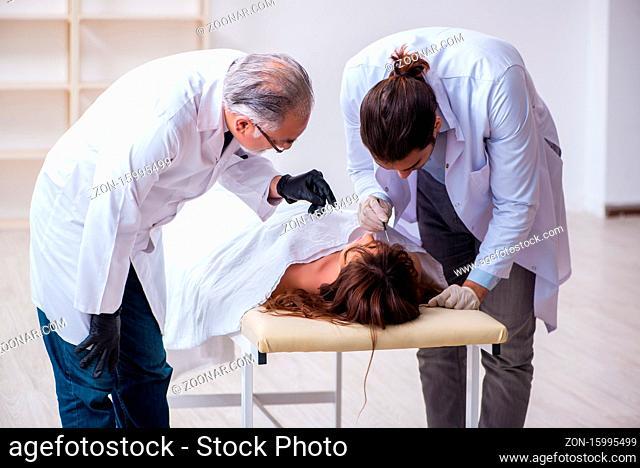 Police coroner examining dead body corpse in the morgue