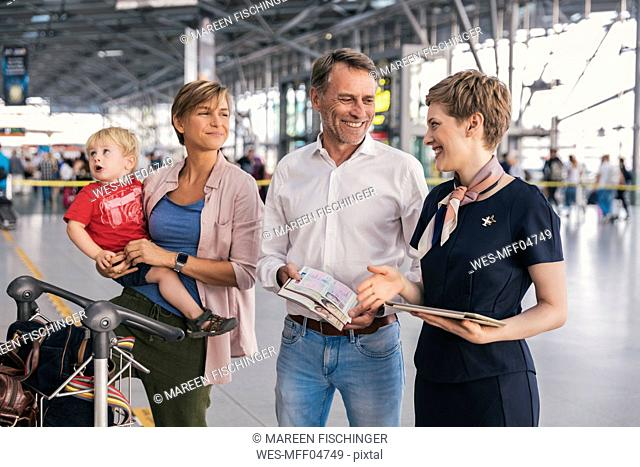 Happy family showing passports to airline employee at the airport