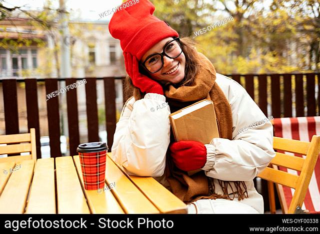Young woman smiling while sitting with book at sidewalk cafe