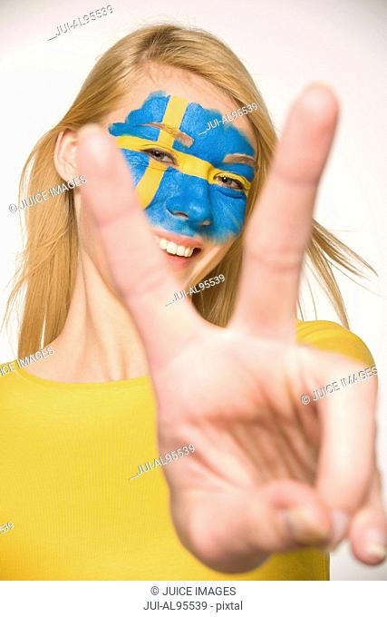 Young woman with Swedish flag painted on face