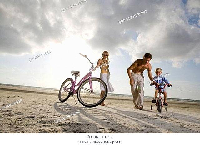 Parents with son riding cycle at the beach