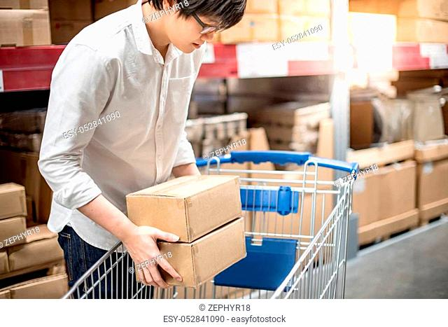 Young Asian man putting paper boxes into trolley cart in warehouse, shopping warehousing concept