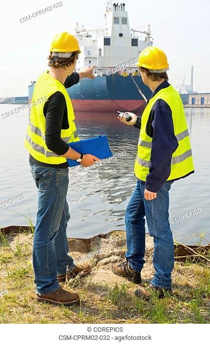 Two harbor engineers, or dockers, in discussion over a large industrial oil tanker