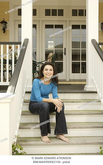 Hispanic woman sitting on porch stairs smiling