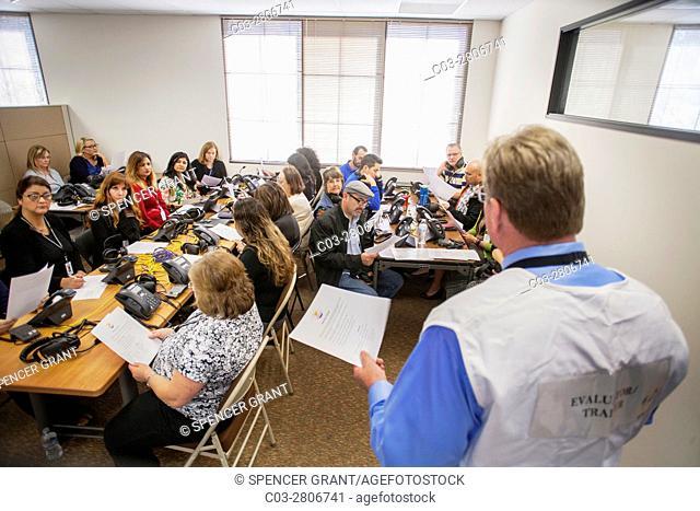 Multiracial volunteer teachers participate in an Emergency Operations Center practice alert phone bank in San Juan Capistrano, CA